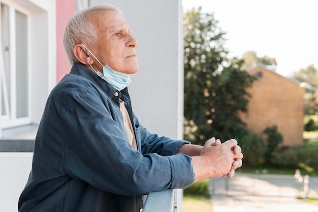 Seitenansicht alter mann mit maske am kinn Premium Fotos