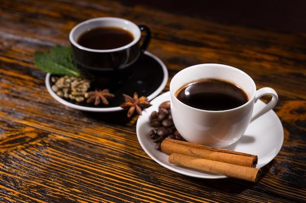 Seitenansicht auf dampfenden heißen schwarzen und weißen tassen tee mit bohnen und kräutern in untertasse auf holztisch Premium Fotos