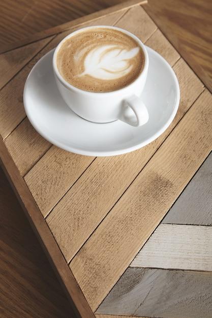 Seitenansicht auf tasse mit cremigem cappuccino latte mit milchigem schaum oben in blattform isoliert auf holzplatte mit muster. auf dem tisch in der café-ladenpräsentation. Kostenlose Fotos