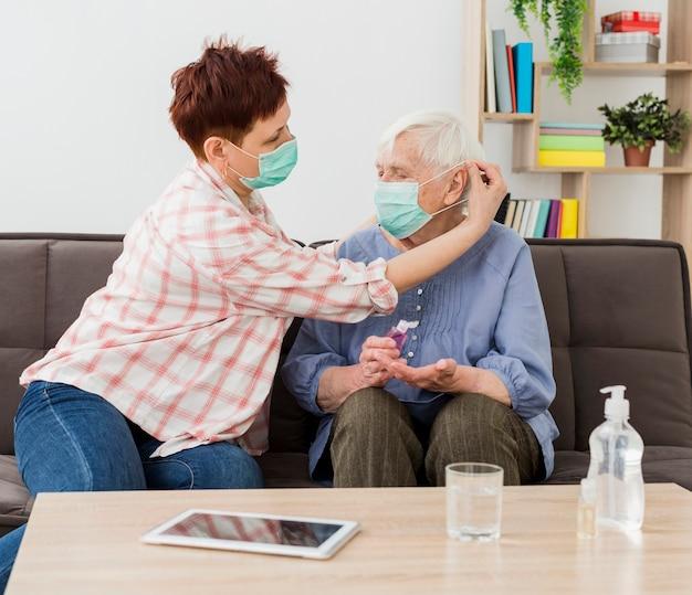 Seitenansicht der älteren frauen zu hause, die medizinische masken tragen Kostenlose Fotos