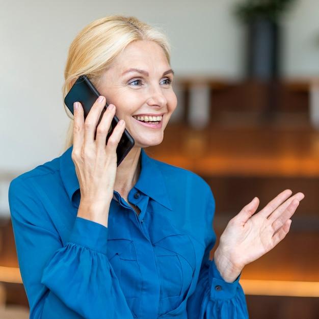 Seitenansicht der älteren smiley-frau, die am telefon während der arbeit spricht Kostenlose Fotos