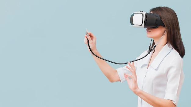 Seitenansicht der ärztin unter verwendung des stethoskops und des virtual-reality-headsets Kostenlose Fotos