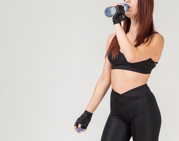 Seitenansicht der athletischen frau, die von einer wasserflasche trinkt Kostenlose Fotos