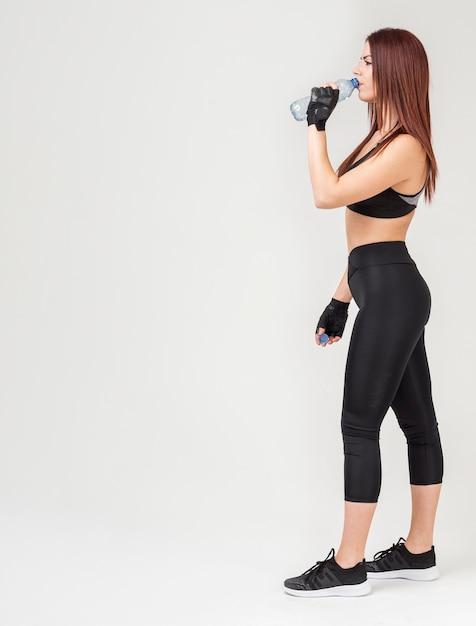 Seitenansicht der athletischen frau in der sportkleidung trinkwasser Kostenlose Fotos