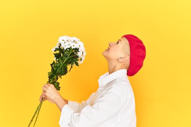 Seitenansicht der aufgeregten überglücklichen älteren frau in der stilvollen baskenmütze und im freizeithemd, die gegen leeren gelben studiowandhintergrund aufhalten, der blumen hält und nach oben schaut, als würde er blumenstrauß werfen Kostenlose Fotos