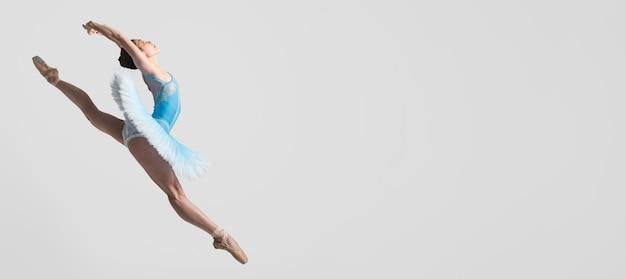 Seitenansicht der ballerina in der luft mit kopierraum Kostenlose Fotos