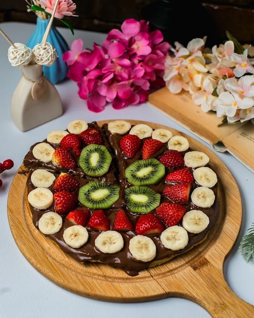 Seitenansicht der belgischen waffel bedeckt mit dunkler schokolade und früchten auf einem holzbrett Kostenlose Fotos