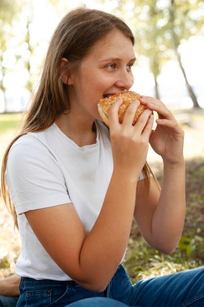 Seitenansicht der frau am park, der burger isst Kostenlose Fotos