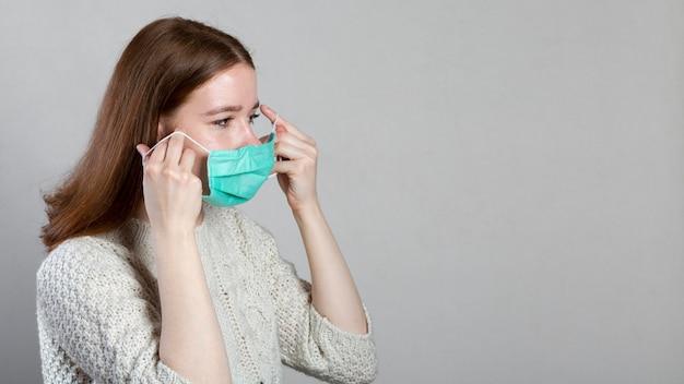 Seitenansicht der frau, die medizinische maske mit kopienraum aufsetzt Kostenlose Fotos