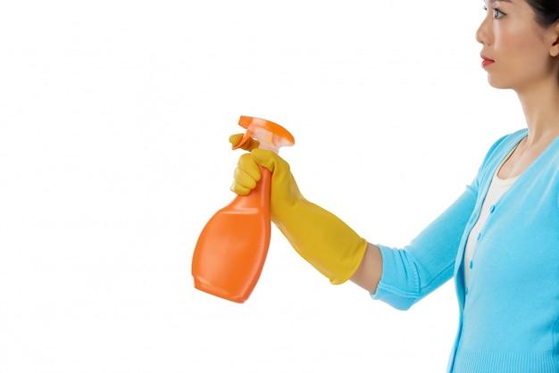 Seitenansicht der frau, die sprayreiniger gegen weißes hintergrund copyspace verwendet Kostenlose Fotos