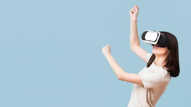 Seitenansicht der frau, die unter verwendung des virtual-reality-headsets spielt Kostenlose Fotos
