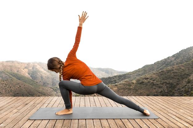 Seitenansicht der frau draußen in der natur, die yoga auf matte tut Kostenlose Fotos