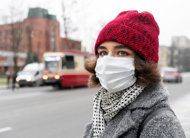 Seitenansicht der frau in der stadt mit der medizinischen maske Kostenlose Fotos
