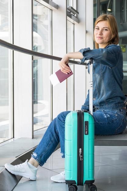 Seitenansicht der frau kamera im flughafen gegenüberstellend Kostenlose Fotos