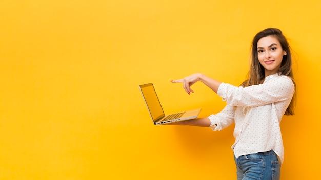 Seitenansicht der frau laptop halten und auf ihn mit kopienraum zeigend Kostenlose Fotos