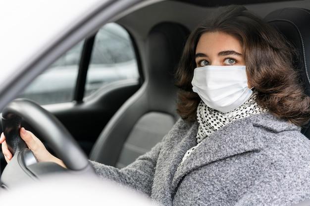Seitenansicht der frau mit der medizinischen maske, die auto fährt Kostenlose Fotos