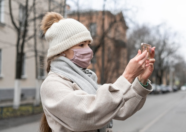 Seitenansicht der frau mit der medizinischen maske, die einen videoanruf im freien hat Kostenlose Fotos