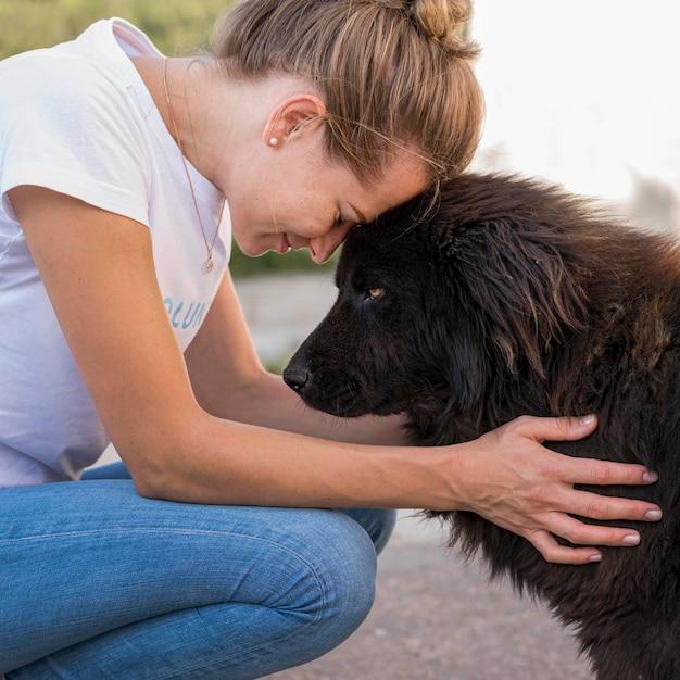 Seitenansicht der frau mit flauschigem schwarzen hund im freien Kostenlose Fotos
