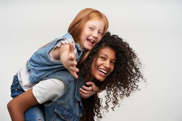 Seitenansicht der freudigen hübschen jungen dunkelhäutigen brünetten frau, die auf ihrem rücken fröhliches niedliches rothaariges weibliches kind reitet, glücklich schaut und breit lächelt, lokalisiert auf weiß Kostenlose Fotos