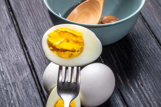Seitenansicht der gekochten eihälfte mit gabel auf rustikalem holz Kostenlose Fotos
