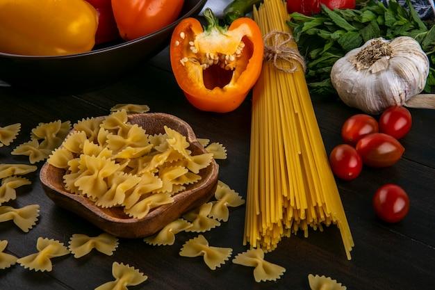 Seitenansicht der hälften der mehrfarbigen paprika mit rohen spaghetti und nudelknoblauch und tomaten auf einer holzoberfläche Kostenlose Fotos