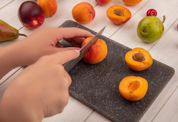 Seitenansicht der hände, die pfirsich mit messer und halb geschnittenem pfirsich auf schneidebrett mit muster von birnenpfirsichen auf hölzernem hintergrund schneiden Kostenlose Fotos