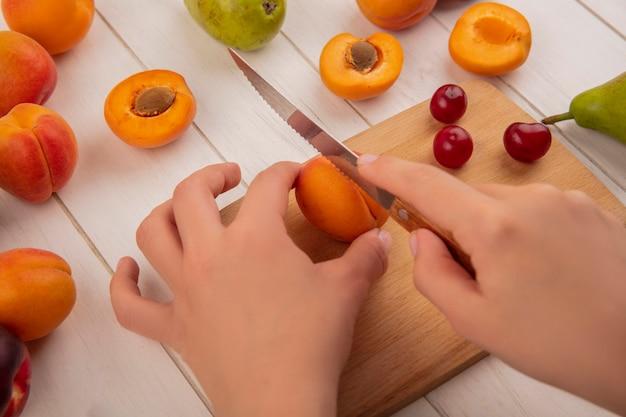 Seitenansicht der hände, die pfirsich mit messer und kirschen auf schneidebrett mit muster von birnenpfirsichen auf hölzernem hintergrund schneiden Kostenlose Fotos
