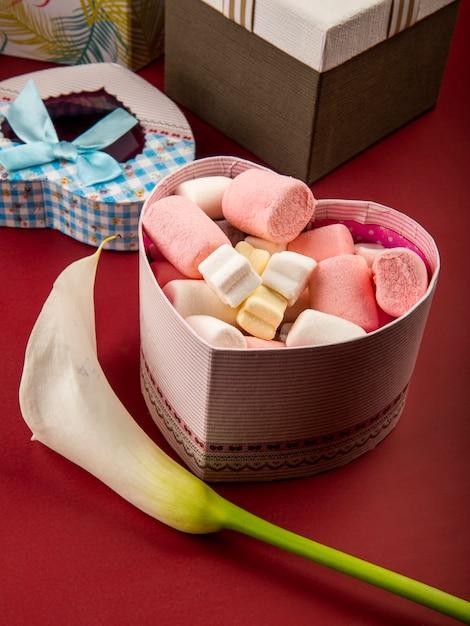 Seitenansicht der herzförmigen geschenkbox gefüllt mit marshmallow und weißer callalilie auf rotem tisch Kostenlose Fotos