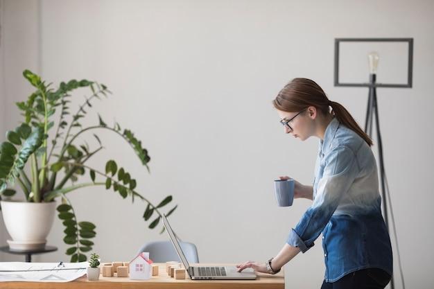 Seitenansicht der jungen frau kaffeetasse beim arbeiten halten an laptop am arbeitsplatz Kostenlose Fotos