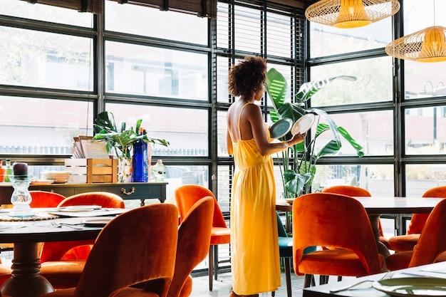 Seitenansicht der jungen frau zwei verschiedene platten im restaurant betrachtend Kostenlose Fotos