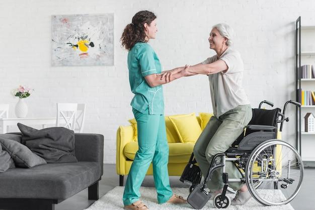 Seitenansicht der krankenschwester die hand des älteren frauenpatienten halten, die vom rollstuhl steht Kostenlose Fotos