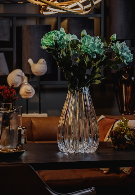 Seitenansicht der modernen geprägten glasvase mit grünen blumen auf einem holztisch Kostenlose Fotos