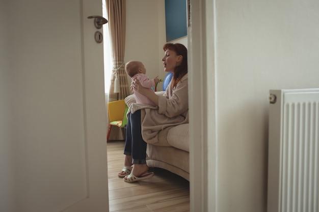 Seitenansicht der mutter mit baby, das auf bett sitzt Kostenlose Fotos