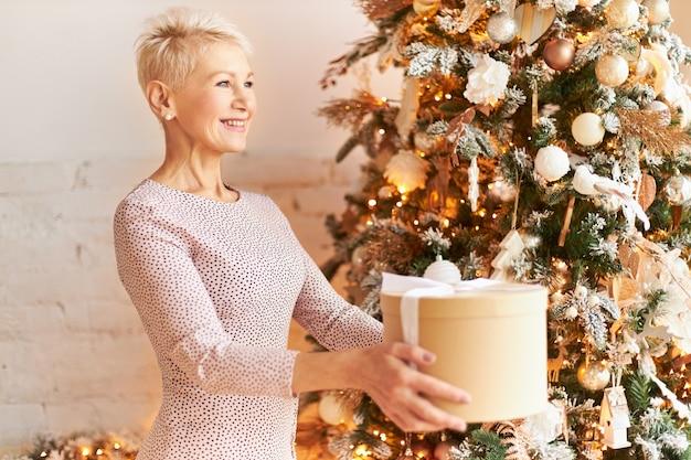 Seitenansicht der positiven frau mittleren alters im schönen kleid, das weihnachtsgeschenke gibt. reife frau mit blonden kurzen haaren posiert am neujahrsbaum, streckt die hände aus, hält die schachtel und lächelt glücklich Kostenlose Fotos