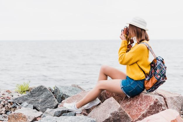 Seitenansicht der reisenden frau ein foto machend Kostenlose Fotos