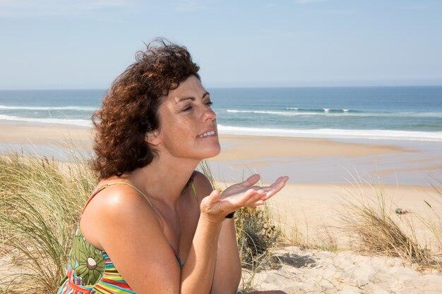 Seitenansicht der ruhigen frau sitzend auf sandigem strand Premium Fotos