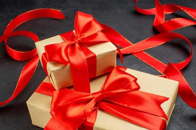 Seitenansicht der schönen geschenke mit rotem band auf dunklem hintergrund Kostenlose Fotos
