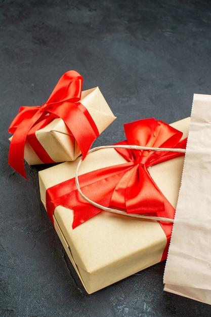 Seitenansicht der schönen geschenke mit rotem band auf einem dunklen tisch Kostenlose Fotos