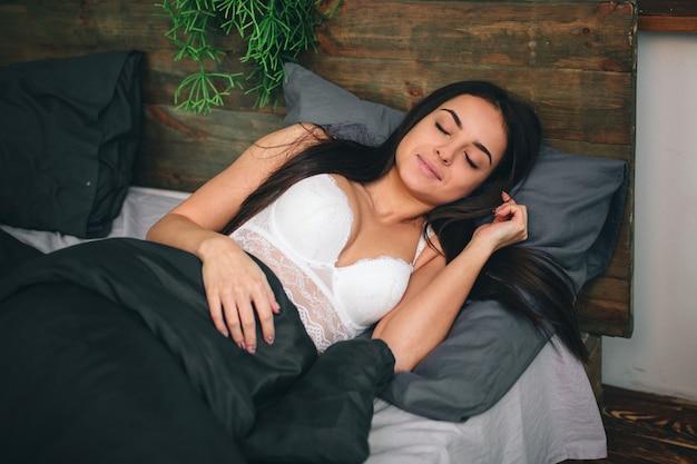 Seitenansicht der schönen jungen frau lächelnd, während sie in ihrem bett zu hause schläft Premium Fotos