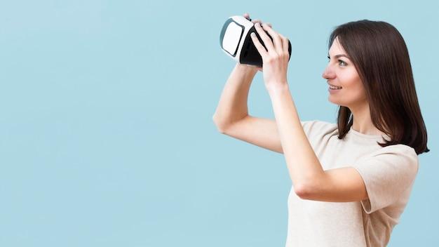 Seitenansicht der smiley-frau, die durch virtual-reality-headset schaut Kostenlose Fotos