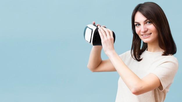 Seitenansicht der smiley-frau, die virtual-reality-headset hält Kostenlose Fotos