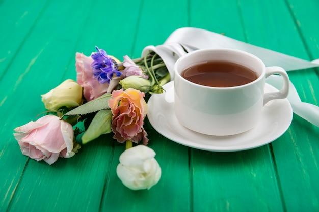 Seitenansicht der tasse tee auf untertasse und blumenstrauß auf grünem hintergrund Kostenlose Fotos