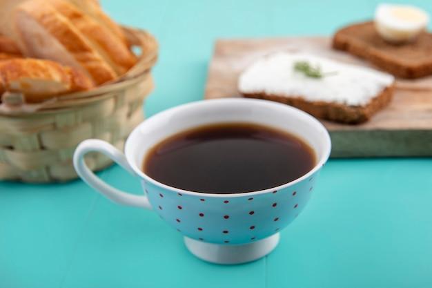 Seitenansicht der tasse tee mit geschnittenem baguette und roggenbrotscheiben, die mit käse und ei mit dillstück auf blauem hintergrund verschmiert sind Kostenlose Fotos