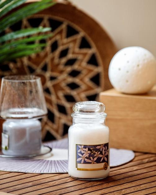 Seitenansicht der vanille-duftkerze im glas auf holztisch Kostenlose Fotos