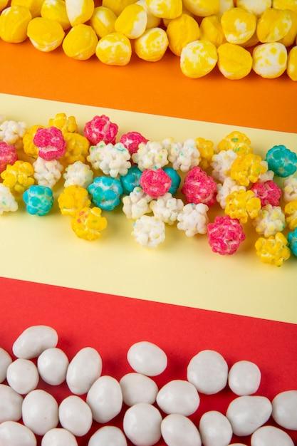Seitenansicht der verschiedenen bunten süßen zuckersüßigkeiten auf dreifarbigem hintergrund Kostenlose Fotos