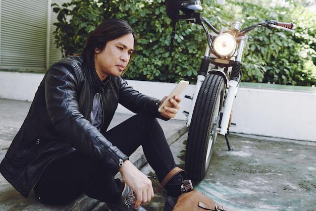 Seitenansicht des asiatischen mannes in der lederjacke sittibg am motorrad mit smartphone draußen Kostenlose Fotos