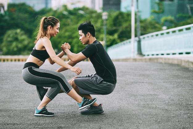 Seitenansicht des athletischen mannes und der frau, die ein bein tun, hocken zusammen draußen Kostenlose Fotos