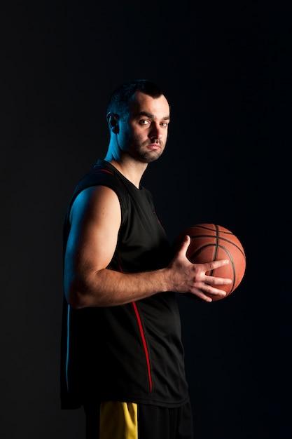 Seitenansicht des basketballspielers aufwerfend beim halten des balls Kostenlose Fotos