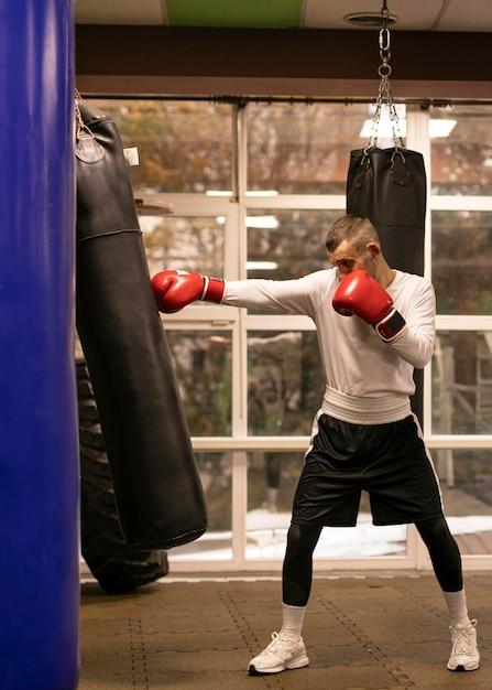 Seitenansicht des boxers, der mit boxsack neben ring übt Kostenlose Fotos