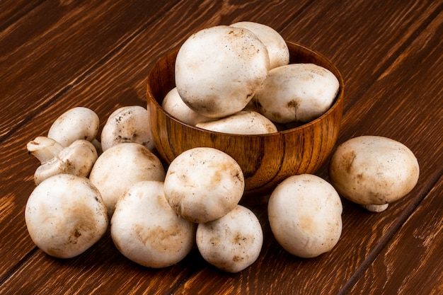 Seitenansicht des champignons der frischen pilze in einer schüssel auf rustikalem hölzernen hintergrund Kostenlose Fotos